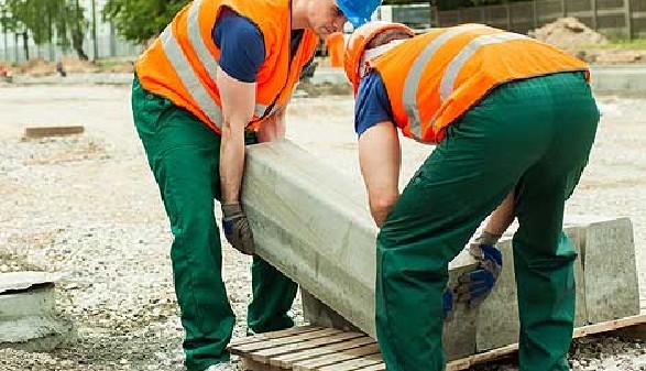 Bauarbeiter heben einen schweren Betonblock © Photographee.eu, Fotolia.com
