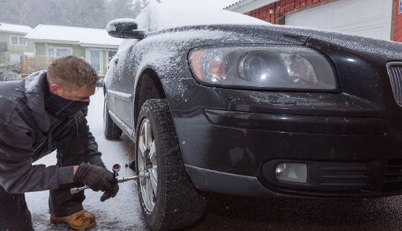 Mann wechselt die Reifen an seinem Auto - es ist Winter © Martin Carlsson, stock.adobe.com