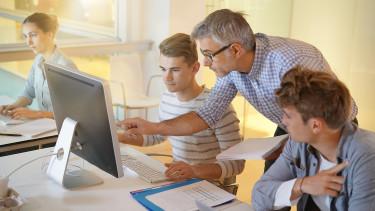 Lehrer erklärt Schüler etwas und zeigt auf den Bildschirm © goodluz , stock.adobe.com