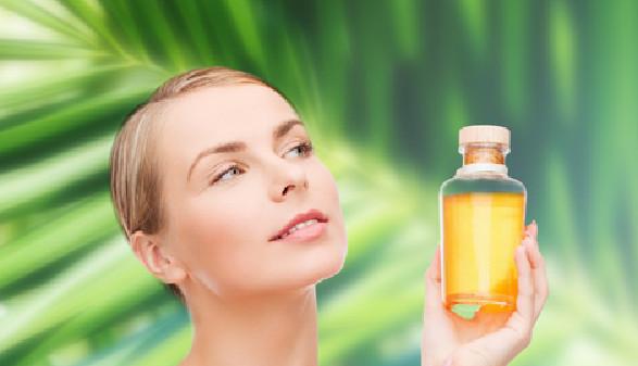 Frau hält Flasche mit Öl in der Hand im Hintergrund Palmwedel © Syda Productions, Fotolia.com