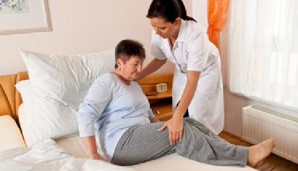 Pflegehilfe hilft Frau aus dem Bett © Gina Sanders, Fotolia.com