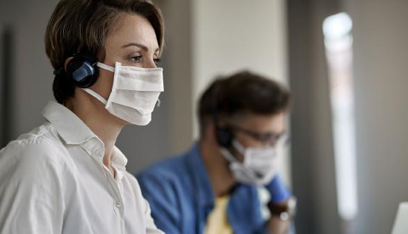 Mitarbeiterin in einem Callcenter mit Mund-Nasenschutz © Drazen, stock.adobe.com
