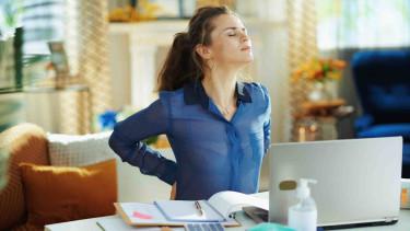 Frau macht eine Dehnungsübung - sitzt vor einem Laptop © Alliance, stock.adobe.com