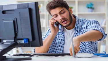 Mann telefoniert mit dem Handy und sitzt vor einem Computer © Elnur, stock.adobe.com