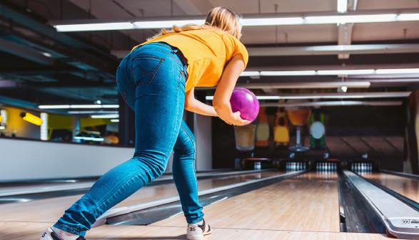 Frau mit Bowlingkugel auf Kegelbahn © Karanov images , stock.adobe.com