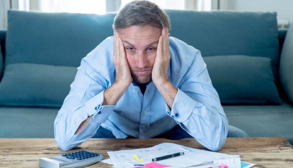 Verzweifelter Mann sitzt auf dem Sofa und stützt den Kopf in die Hände © samuel, stock.adobe.com