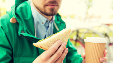 Junger Mann hält Sandwichbrötchen und Coffee to go © Syda Productions , stock.adobe.com