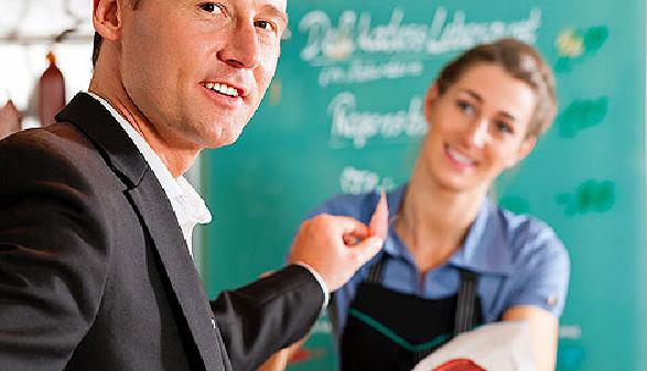Kunde kostet die Wurstprobe, die Verkäuferin anbietet. © Kzenon, stock.adobe.com