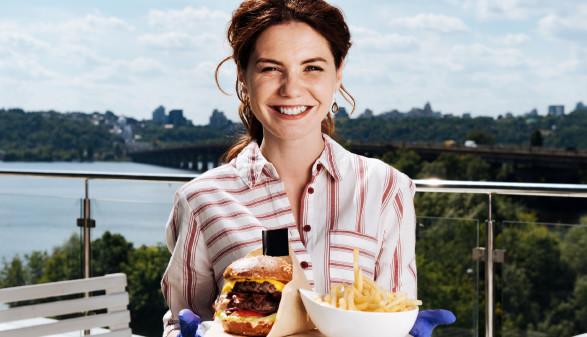 Frau hält Teller mit Burger und Pommes © zinkevych, stock.adobe.com