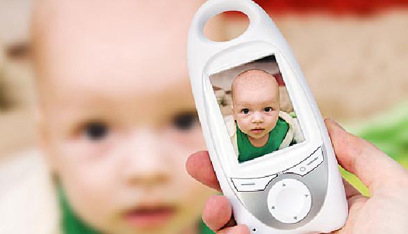 Erwachsene Person hält Babyfon in der Hand - im Hintergrund das Baby © Piotr Adamowicz, Fotolia.com