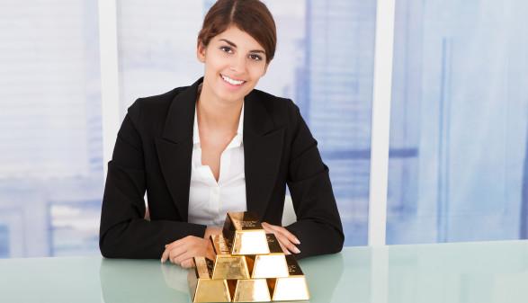 Frau mit Goldbarren vor sich auf dem Tisch © Andrey Popov, stock.adobe.com